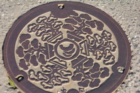 新しくも古いさいたまを表わす盆栽が描かれたマンホールの蓋
